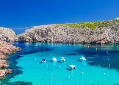 tuulijumala/Shutterstock.com - Cala Morell cove with its red rocks and crystal clear blue water, Menorca island, Balearic Islands, Spain.